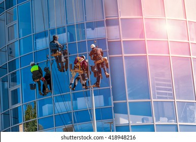 group of workers cleaning windows service on high rise building. work on the heights , industrial mountaineering