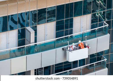 Group of workers in a cradle inspecting facade of high rise building. Aluminium cladding panels facade inspection and maintenance