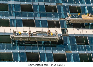 A group of workers in the cradle inspects the facade of a high-rise building. Glass building, inspection and maintenance of the facade. Batumi, Georgia