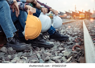 A group of workers holding hard hat and engineers rested on the tracks after their hard work. Teamwork engineer work together in a construction railway.