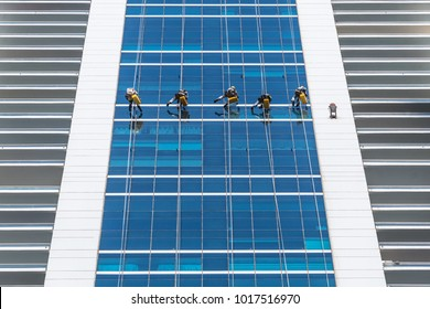 Group of workers wearing safety harness clean windows at height on modern high rise building. Professional rope access. Low angle view