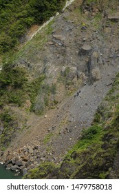 A group of workers worked on cleaning cliff surface in order to get the above road foundation firm