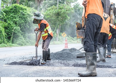 Group of workers working on repairing asphalt road. Workers on a road construction, industry and teamwork.