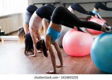 Group workout for women, pilates, fitness, balance, activity and healthy lifestyle. Young female sportsmen doing exercise on sporting balls in gym