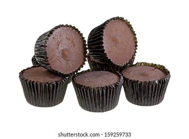 A group of wrapped peanut butter cups with two stacked on top of white background.