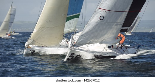 group yacht sailing together at race