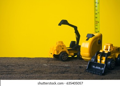 group of yellow construction cars with measuring tape on  yellow background