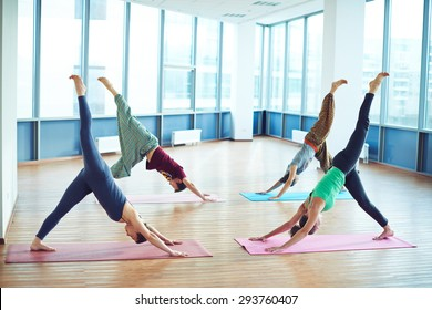 Group of yoga lovers doing exercise on mats in gym