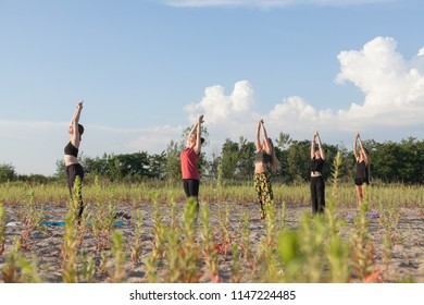 group yoga performing sun salutations in outdoor environment