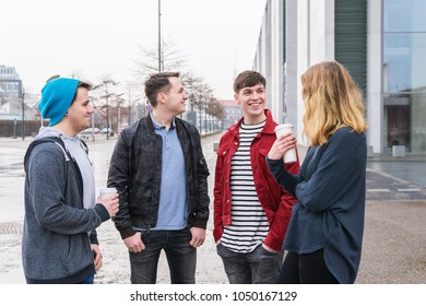 group of young adult friends having a conversation while standing together holding coffee to go cups on city street in Berlin