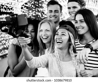 Group of young adult friends taking a group selfie with a selfie stick