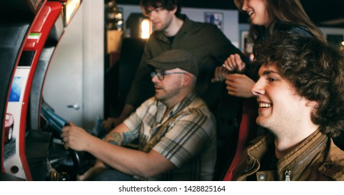 Group of young adults at an arcade, playing pinball and video games.  Series includes video as well.