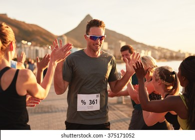 Group of young adults cheering and high fiving a male athlete crossing finish line. Sportsman giving high five to his team after finishing the race.