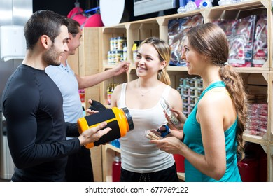 Group of young adults discussing bodybuilding supplements in gym. Focus on the right woman and man