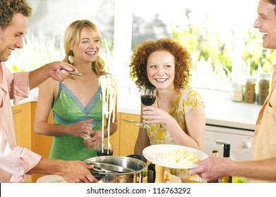 Group of young adults drinking wine and socialising while serving spaghetti for lunch