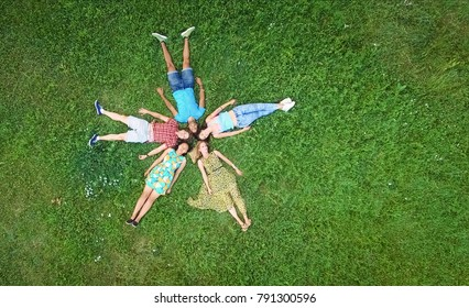 Group of young adults laying in grass in star formation