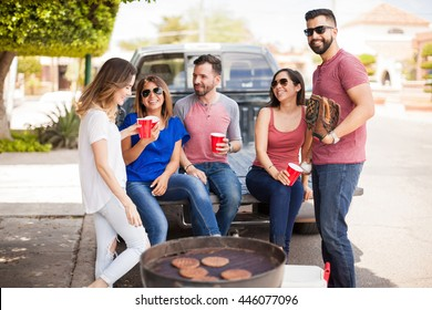 Group of young adults sitting on the back of a pick up truck and talking about a baseball game while drinking and cooking burgers