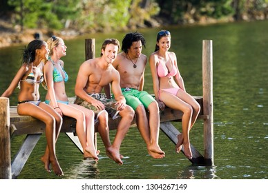 Group of young adults in swimwear on wooden lake jetty at camera