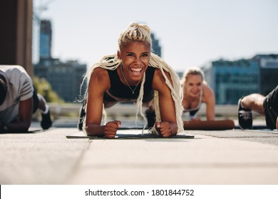 Group of young adults working out together outside in the city. Men and women holding a plank position and smiling.