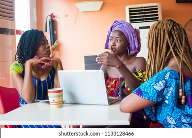 group of young african women discussing something important. three african women discussing business. group of young women discussing together