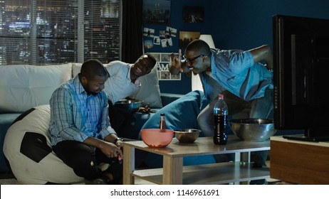 Group of young African-American men chilling on sofa with popcorn and having fun while playing videogame with gamepad one of player loses and start to laugh and tease other player his friend.