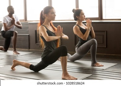 Group of young afro american and caucasian sporty people practicing yoga lesson with instructor standing in anjaneyasana exercise, Horse rider pose, working out, indoor full length, studio