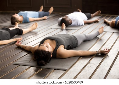 Group of young afro american and caucasian sporty people practicing yoga lesson lying in Dead Body pose, Savasana exercise, working out, resting after practice, indoor close up, studio