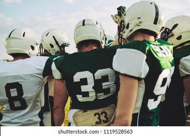 Group of young American football players standing together with their arms raised in a huddle before a game