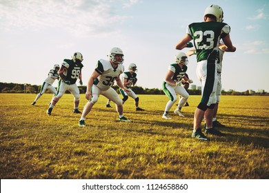 Group of young American football players doing drills while practicing outside together on a grassy field in the afternoon