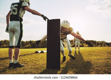 Group of young American football players practicing tackles and defensive drills outside together on a grassy field in the afternoon