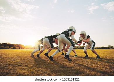 Group of young American football players lining up in formation during a practice session on a sports field on a sunny afternoon