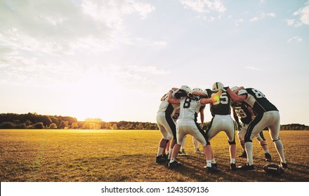 Group of young American football players standing in a huddle together on a sports field in the afternoon discussing before a game