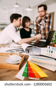 Group of young architects working on a new project, selective focus in the foreground on the drawings and color tables, background image.