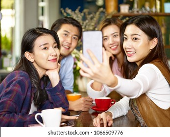 group of young asian adults man and women sitting coffee shop taking a selfie.