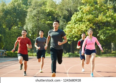 group of young asian athletes male and female training together on track.