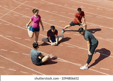 group of young asian athletes stretching relaxing on track before training.