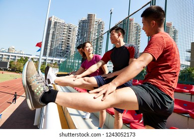 group of young asian athletes warming up pressing legs in stadium.