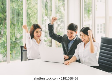 Group of young Asian business people celebrate success with laptop