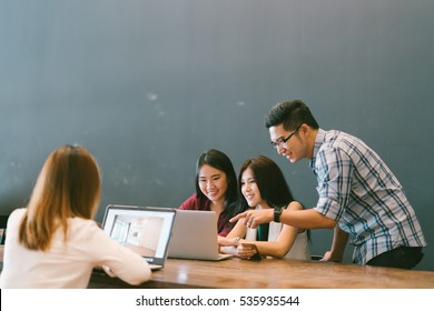Group of young Asian business people in team casual discussion, startup project business meeting or happy teamwork brainstorm concept, with copy space, depth of field effect