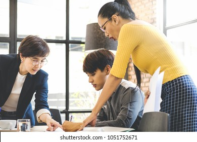 Group of young asian employee brainstorming and working together at modren office workplace. Or Team trainer are teaching trainee man. Internship concept.