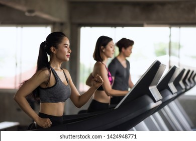 Group of young Asian female and male friends running on treadmills in sport fitness gym. two women and man runn on machine. workout, exercise, training healthy lifestyle.