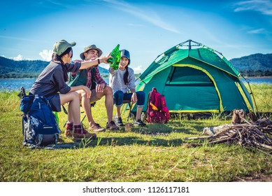 Group of young Asian friends enjoy picnic and party at lake with camping backpack and chair. Young people toasting and cheering bottles of beer. People and lifestyles concept. Outdoor background theme