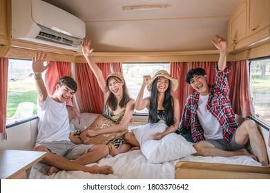 Group of young asian friends having fun inside camper van on weekend