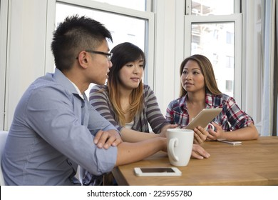 Group of young Asian friends looking at a digital Tablet at home.