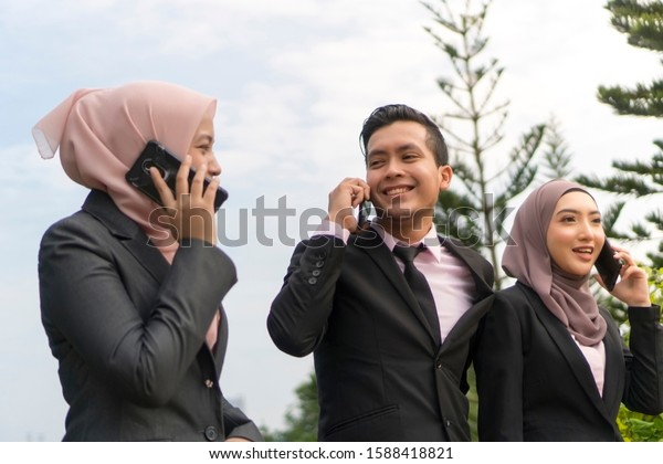 Group of Young Asian Malay Executive at the park wearing suit outdoor holding phone focus on center