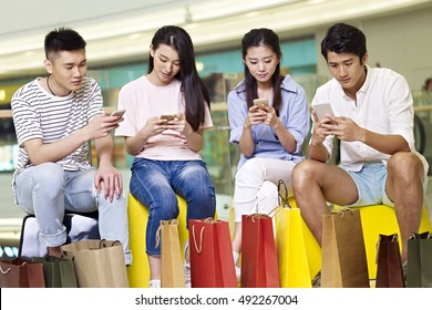 a group of young asian people men and women playing with cellphones while taking a break in shopping mall