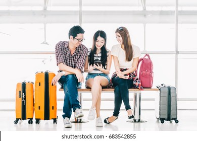 Group of young Asian travelers using smartphone checking flight or online check-in at airport together, with luggage. Travel abroad, summer holiday trip, or mobile phone application technology concept