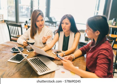 Group of young Asian women, college students in serious business meeting or project brainstorm discussion at coffee shop. With laptop computer, digital tablet, smartphone. Startup or teamwork concept.
