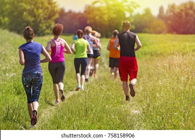 Group of young athlete running marathon outdoors in sunset