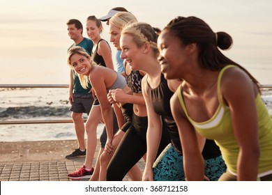 Group of young athletes in start position, focus on woman. Fit young people preparing for race along sea.